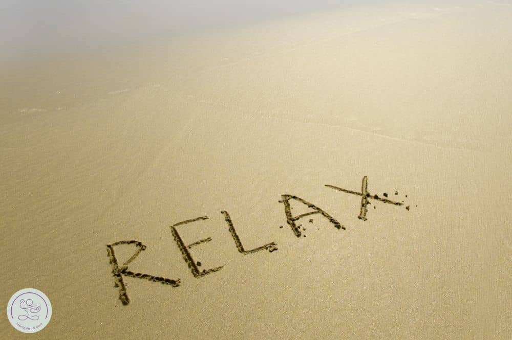 """""""Relax"""" etched in sand, a reminder to relax your pelvic floor when you're body is tense."""