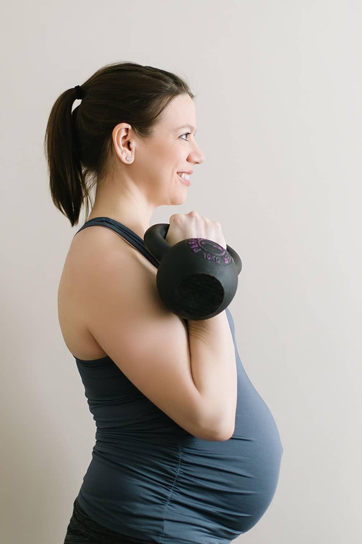 Pregnant athlete holding kettlebell