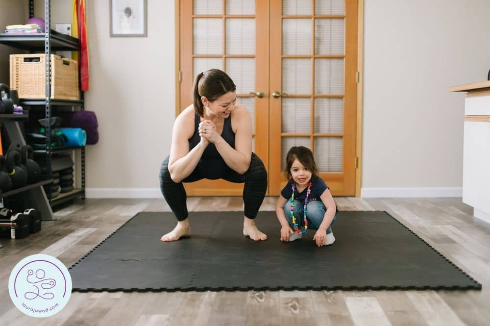 Pregnant mom exercising with daughter in home gym