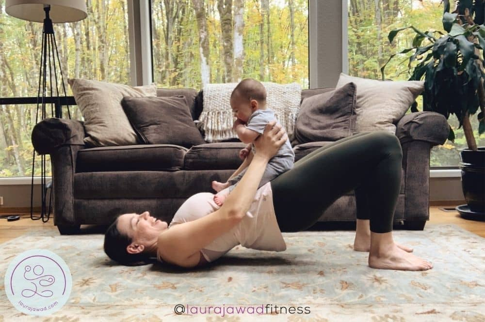 Postpartum mom doing a glute bridge with baby