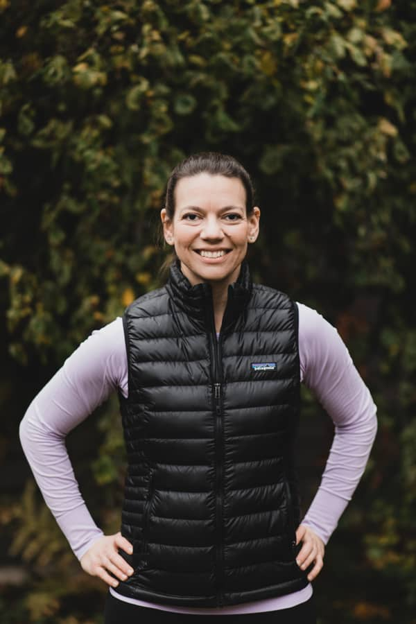 Laura Jawad, online pregnancy and postpartum personal trainer, standing in front of trees.