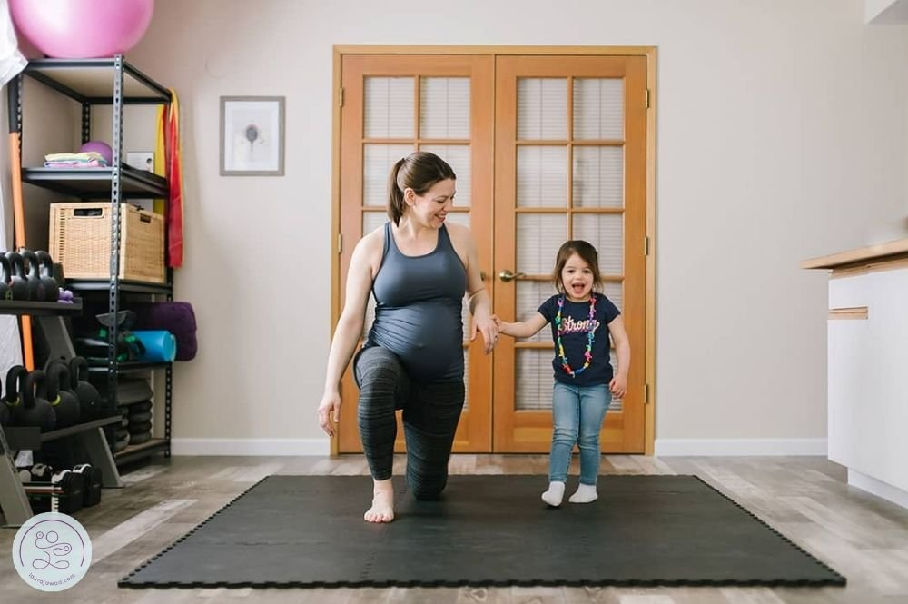 Pregnant woman lunging next to toddler