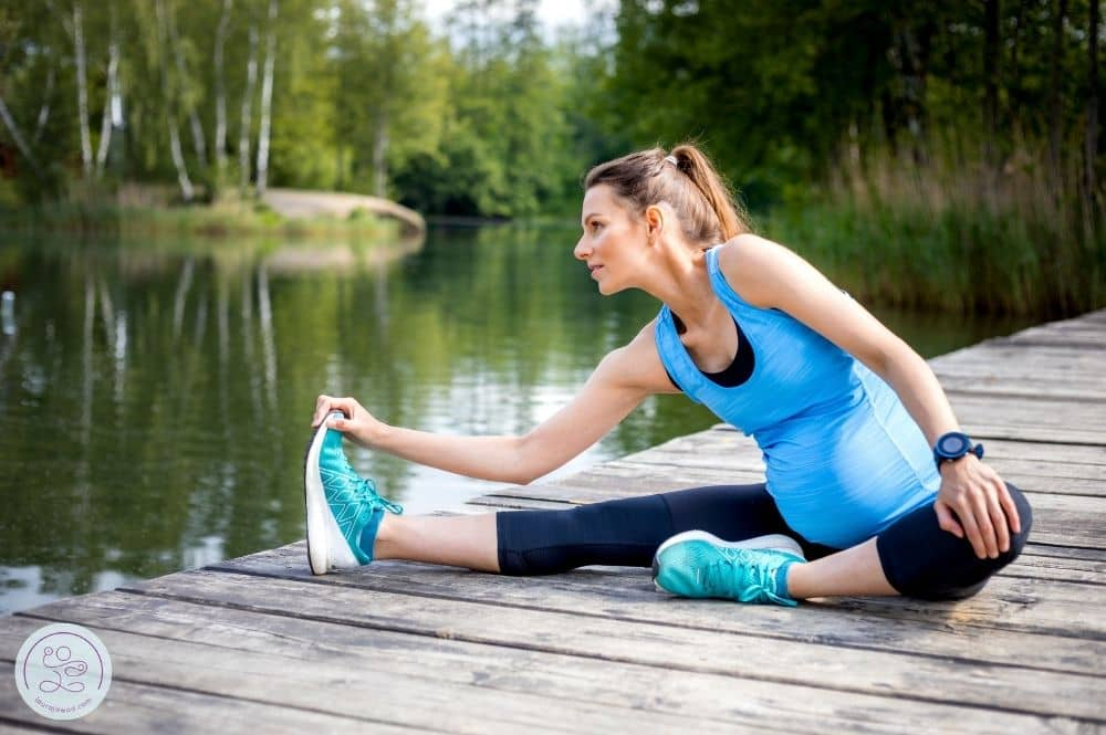 Pregnant runner sitting and stretching after a run