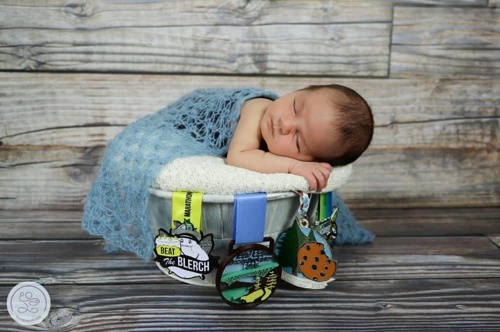 Newborn baby in basket with half marathon race medals